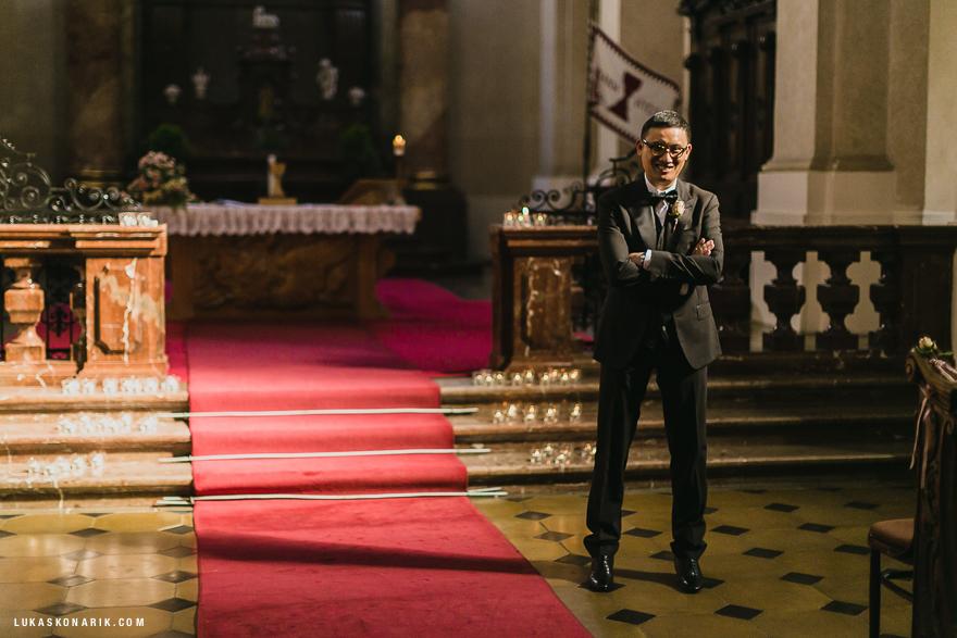 svatební fotografie ženicha v kostele sv. Mikuláše