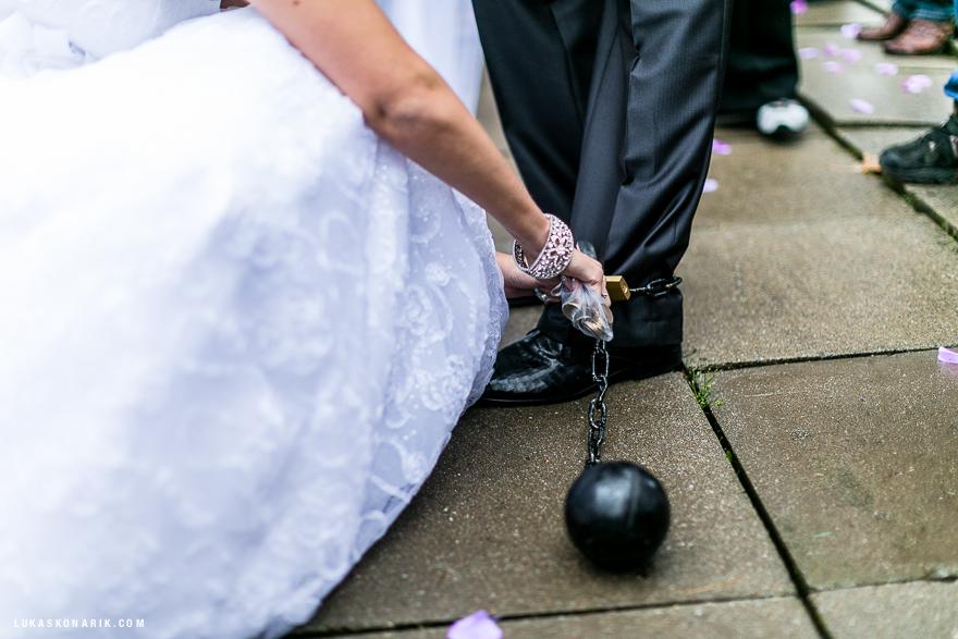 svatební fotografie ženich s koulí u nohy