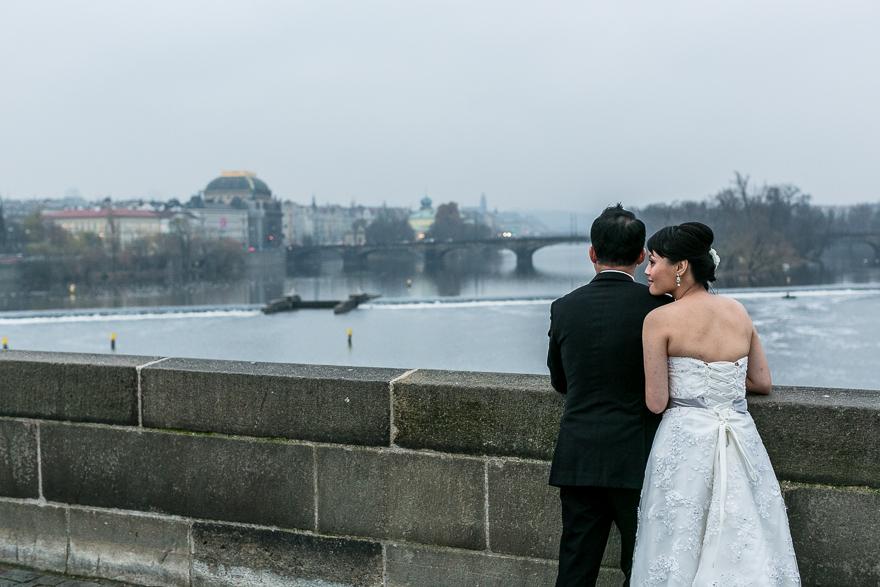 nevěsta a ženich na Karlově mostu s výhledem a Vltavu